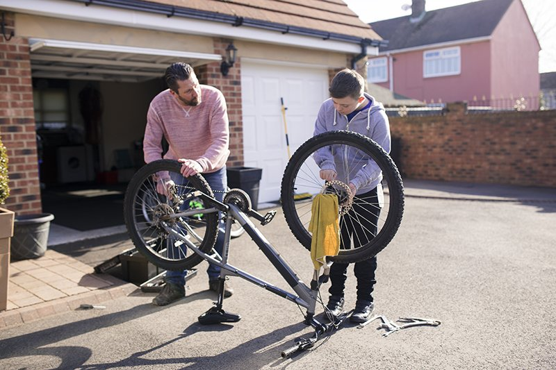 A boy with down syndrome fixes a bike with his father on the driveway.